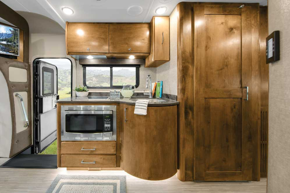 RV interior of oven, wooden cabinetry  with door open to outdoors