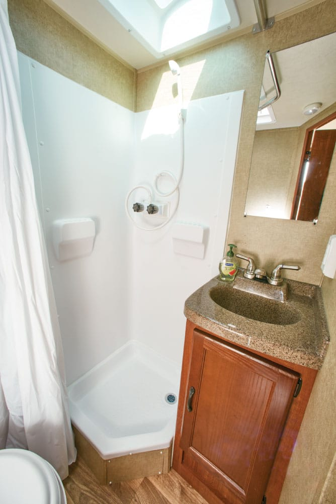 The i18's neo-angle shower opens up floor space in front of the sink and around the toilet. The lavatory features a large medicine cabinet (not shown) and a Granicote counter.