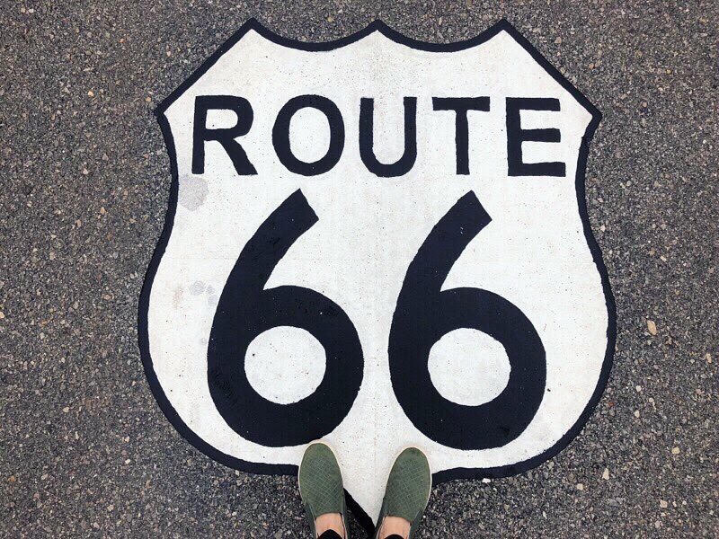 Route 66 painted sign on road with person's feet at bottom