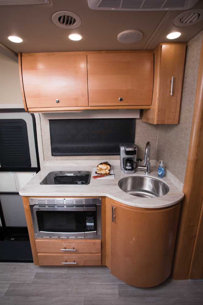 For its compact size, the kitchen is very workable. The solid-surface countertop adds a touch of class, while the sink and appliances are well-placed in the curvy structure.