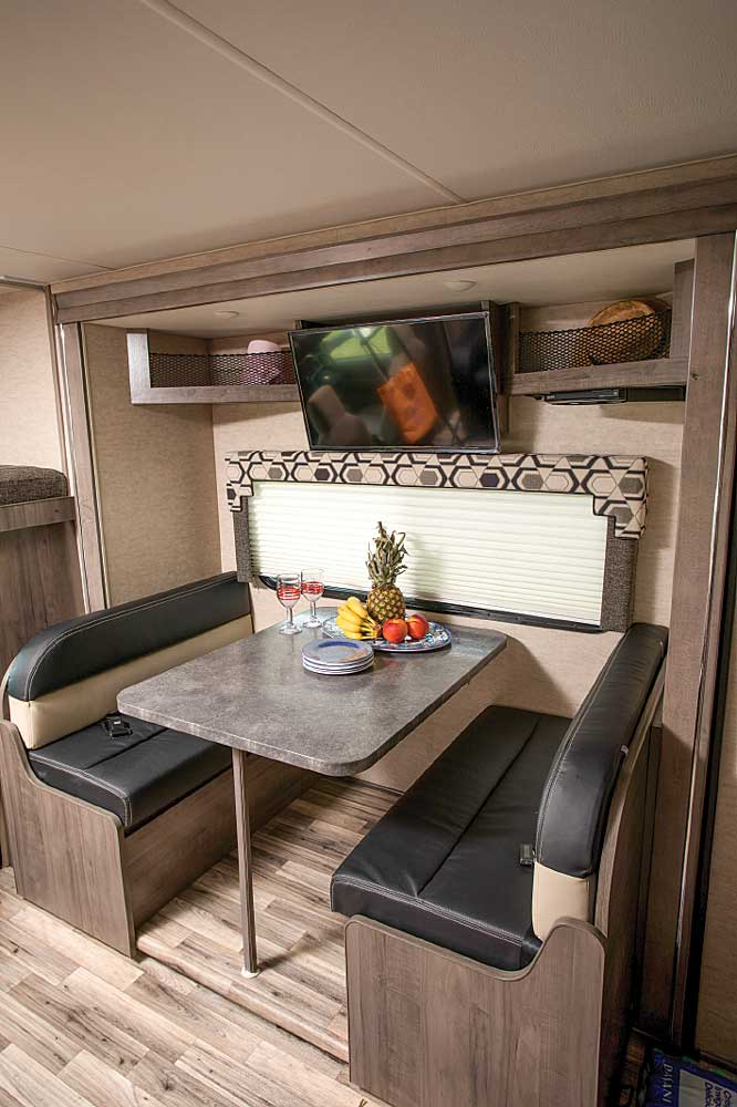 Handy open shelving and a 32-inch HDTV are mounted over the dinette that's housed in the curbside slideout.