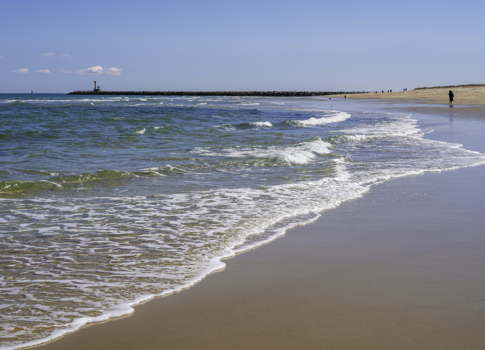 Pristine Scusset Beach seascape in Sagamore at the north end of the Cape Cod Canal. In distance, there are small numbers of people walking and resting.