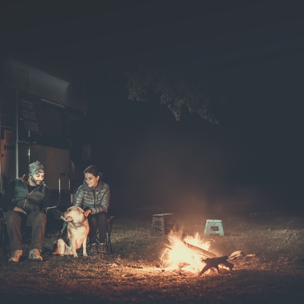 Couple on vacation near campfire and motorhome