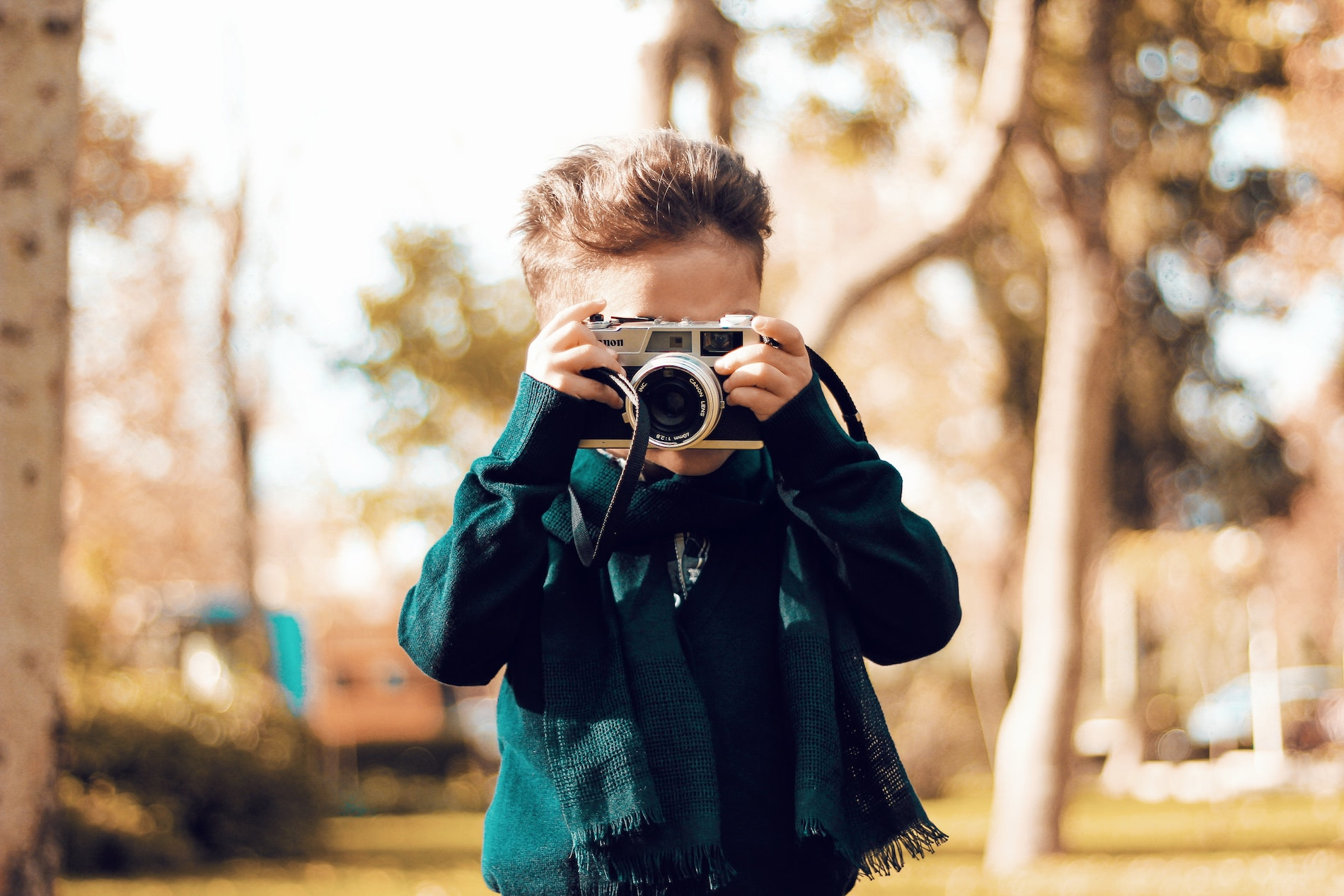 A young kid taking a photo