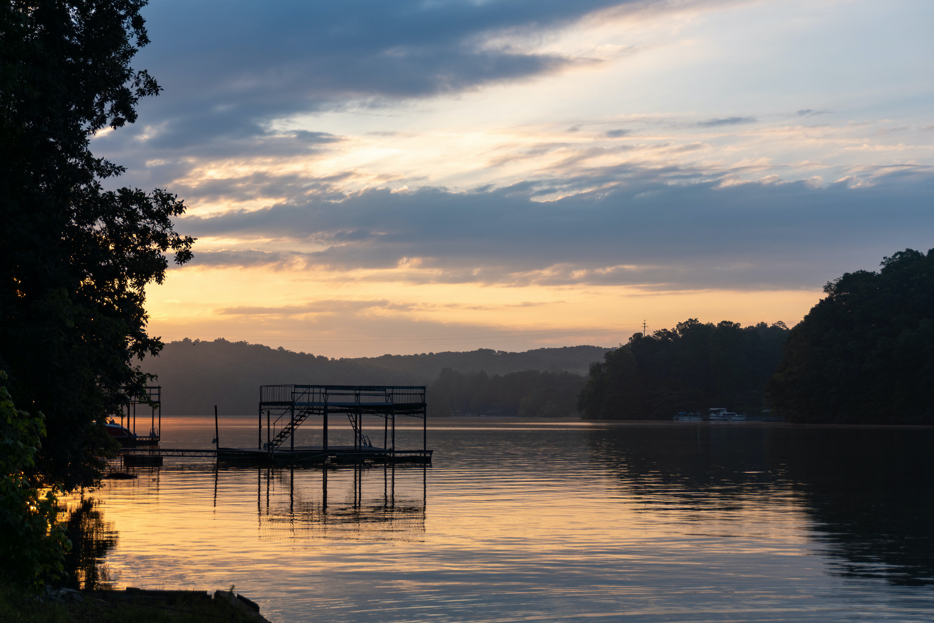 Dawn over Lake Lanier; silhouette of a dock and trees on a lake under a purple and orange sky with clouds; landscape view