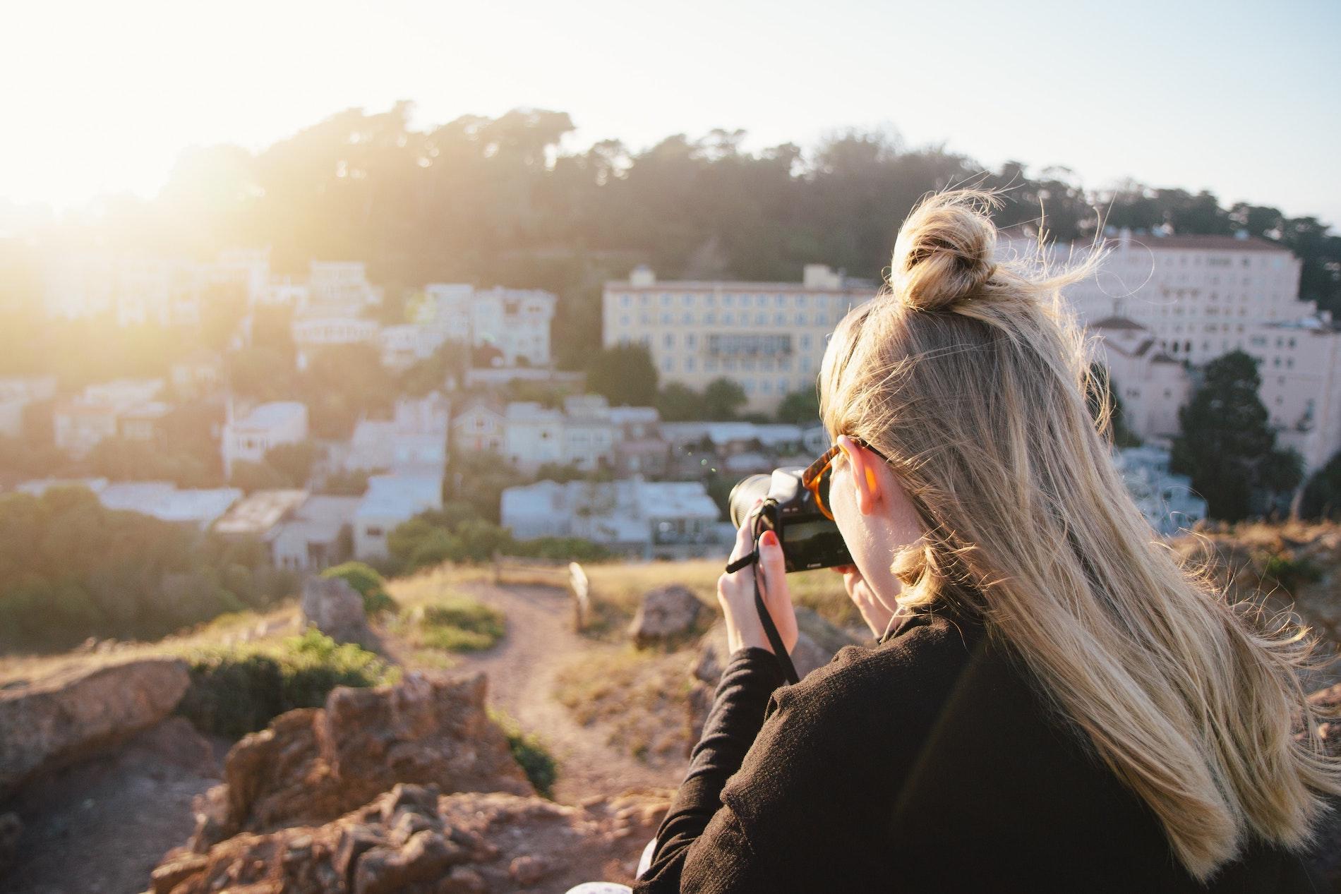 a girl taking a photo facing the sun
