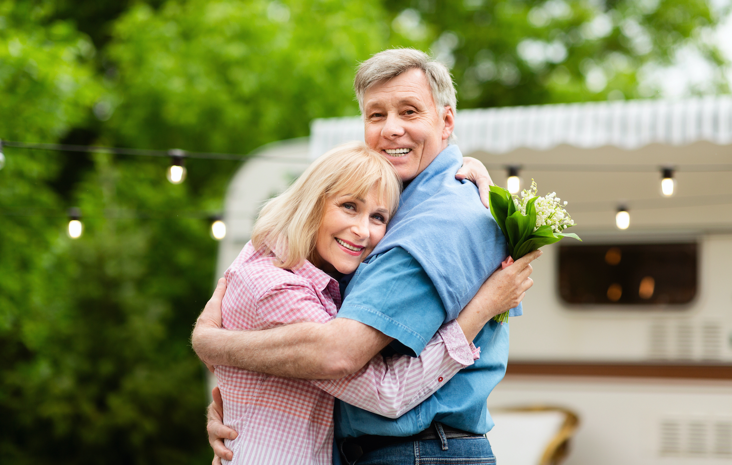 Loving Couple with Camper and Flowers