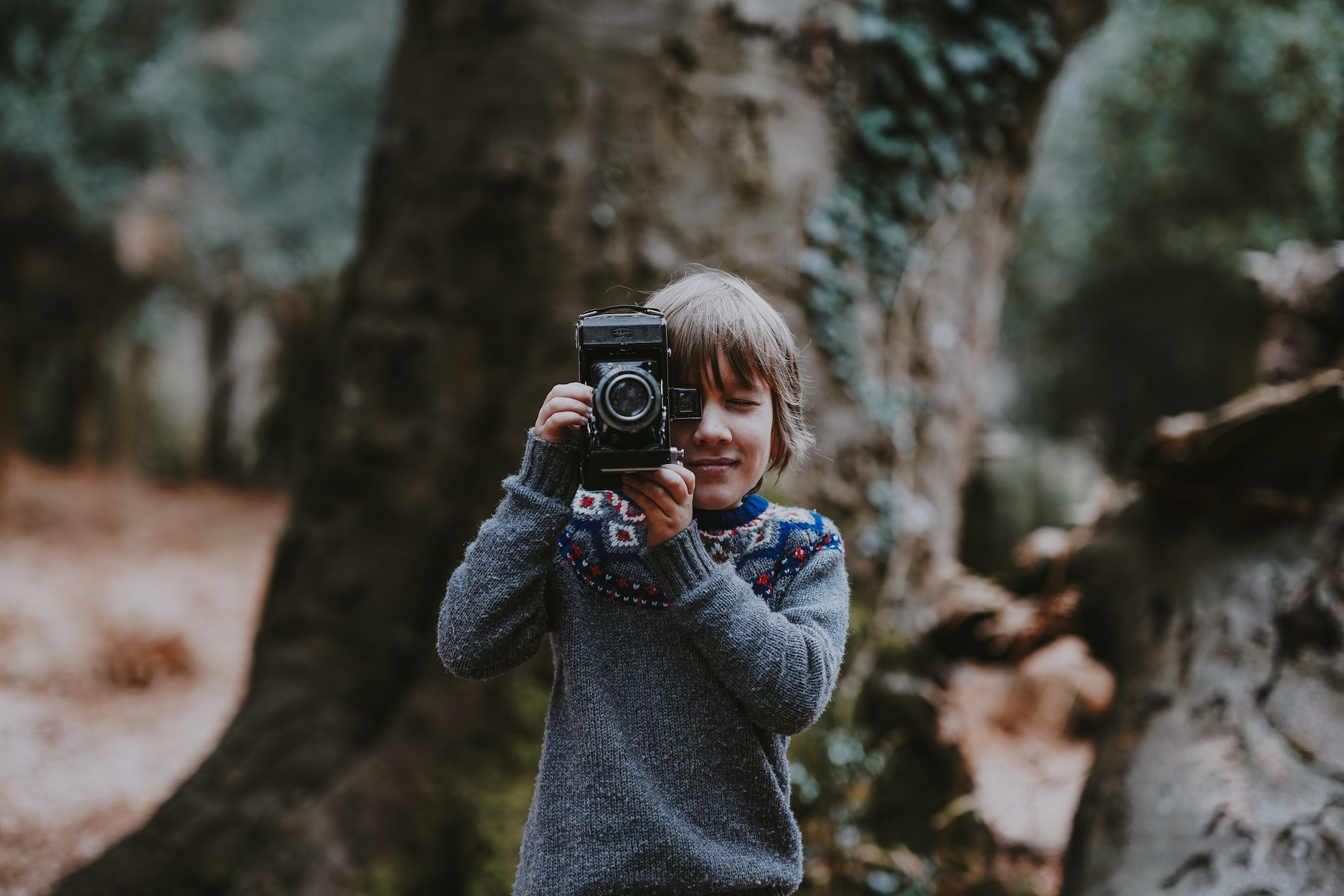 A Young boy taking a picture using an old camera