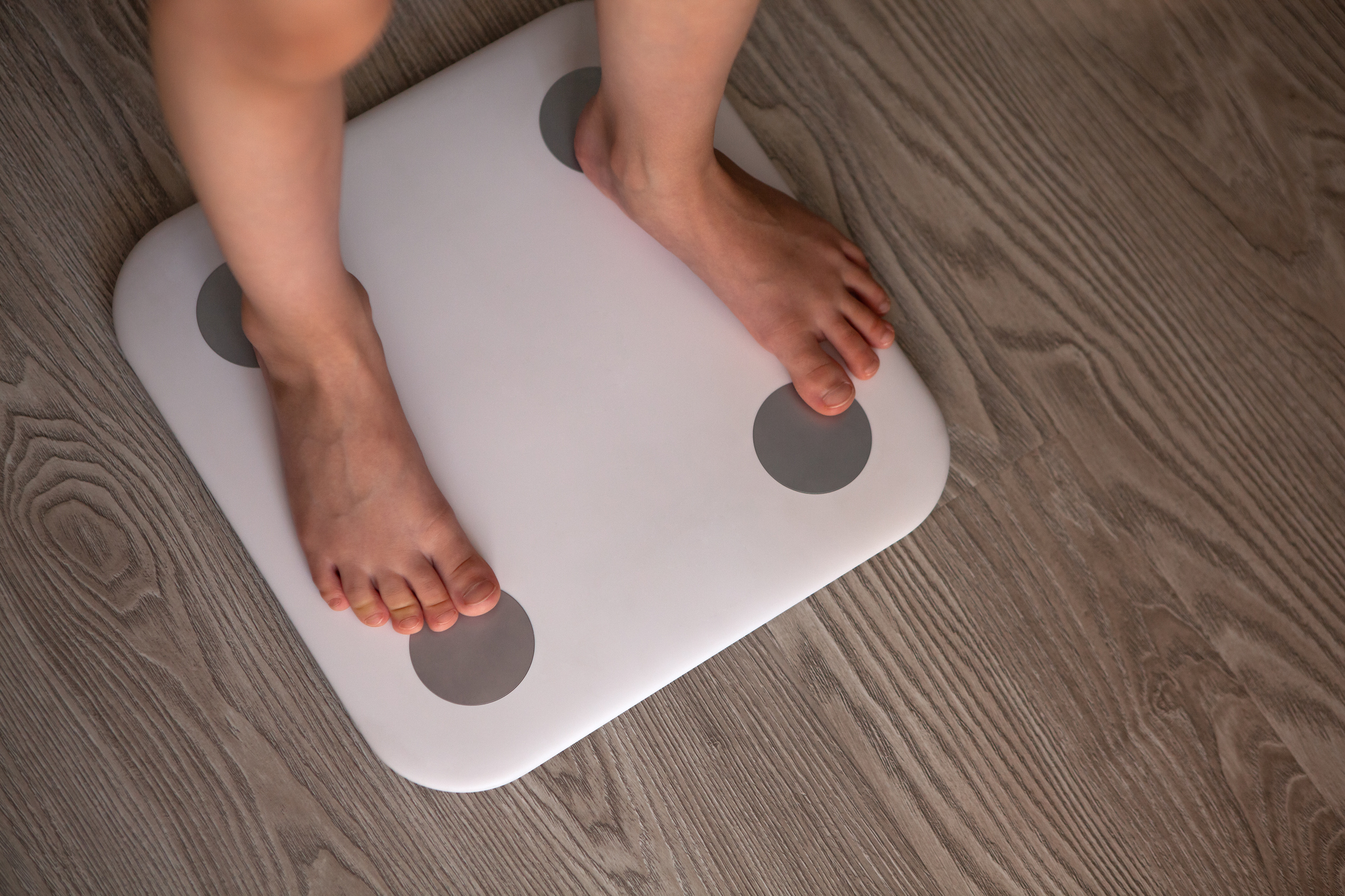 Kid girl or boy stands and weighs himself on white modern electronic smart scale. Scales stand on grey wooden floor. Only legs are visible. Concept of Internet of things, weight control, health.