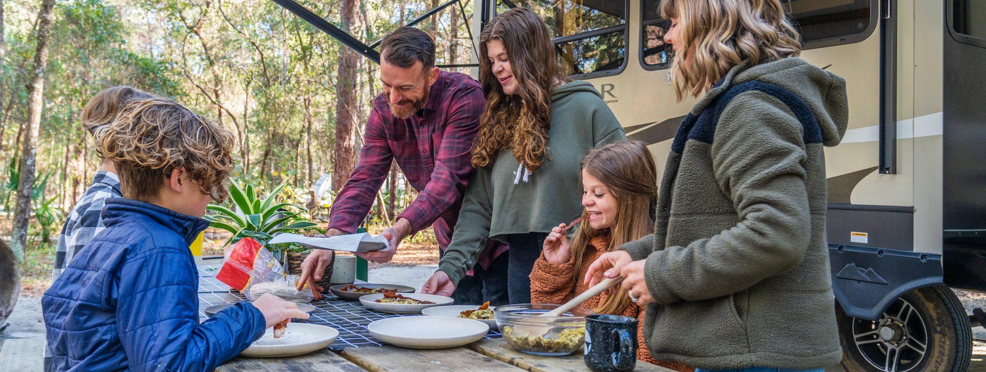 family eating breakfast outside of their RV
