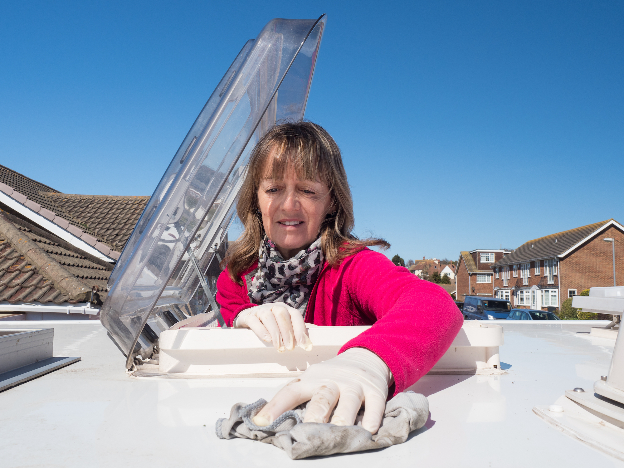 A lady motorhome owner cleans the roof of her vehicle with latex gloves on.The top half of her body is visible as she has climbed through the roof skylight.Vivid pink fleece.Amusing.Image