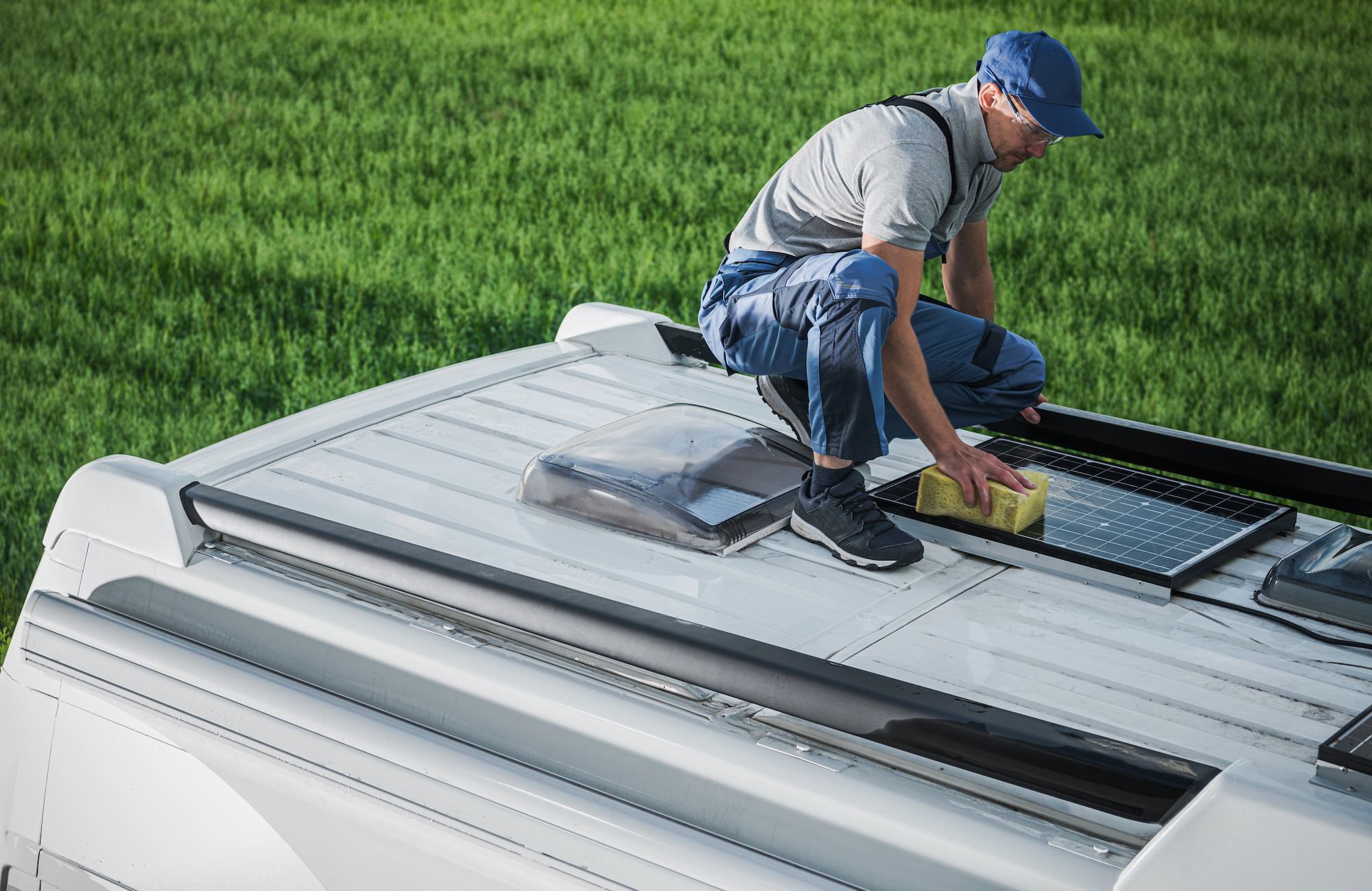 Caucasian Men in His 40s Cleaning Camper Van RV Roof Installed Solar Panels Using Sponge and Soft Washing Detergent. Motorhome Maintenance. RV Industry Theme.