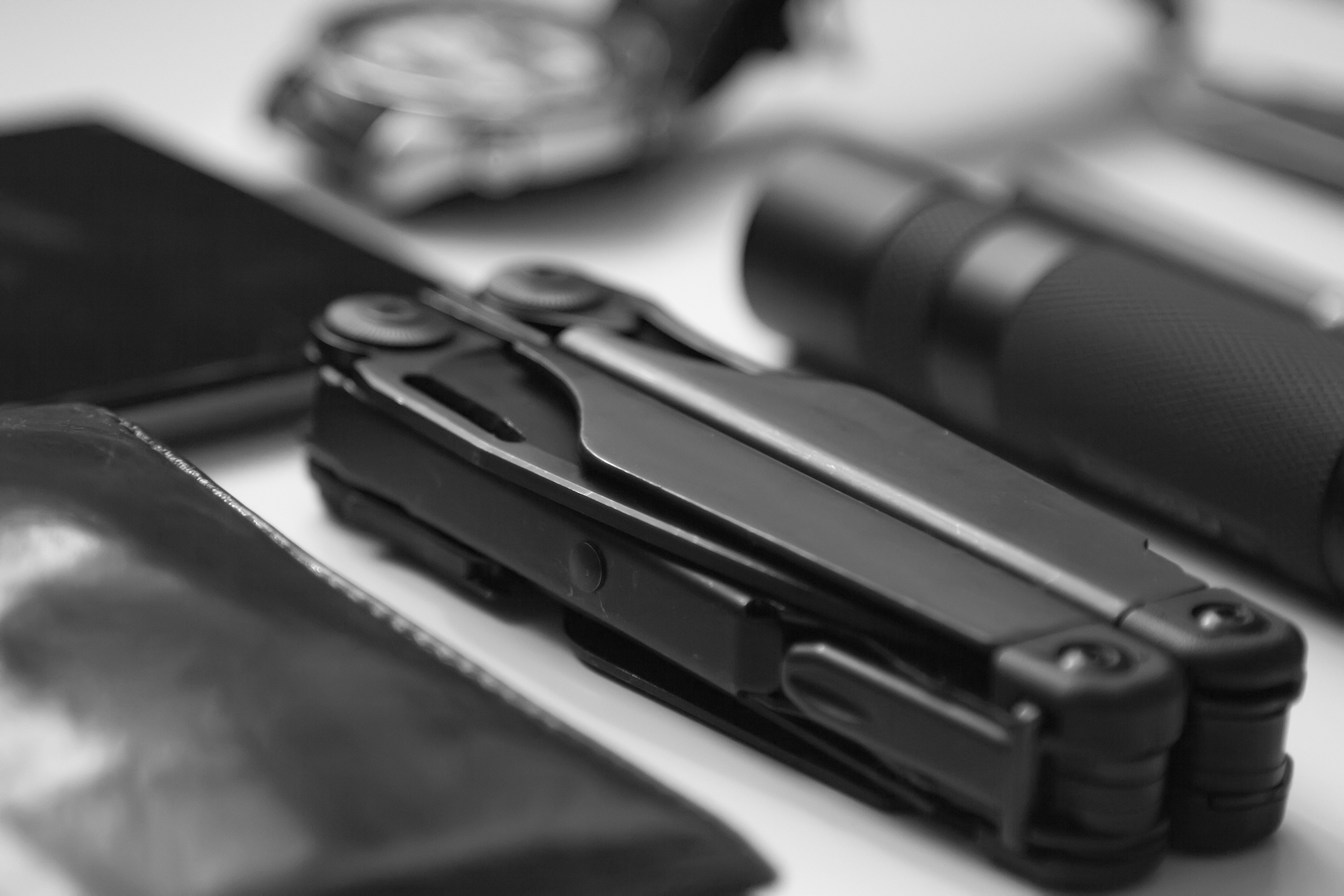 everyday carry ( EDC ) items for men in black color on white background - multi tool ( multitool ) close up on white backround with small depth of field. Modern city set. Business and craft concept