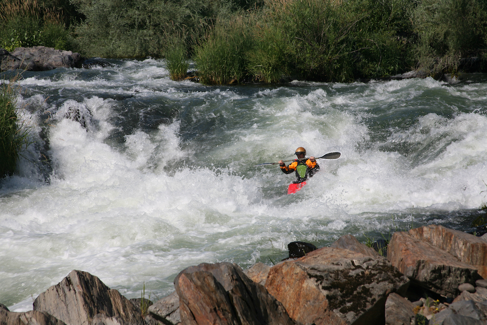A kayaker battling strong rapids on the Rogue River in Oregon