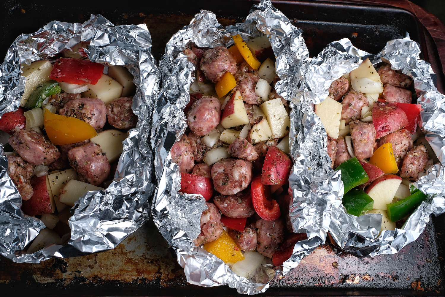 Three foil packets with cut sausages, vegetables, oil and pieces ready to put in oven or grill