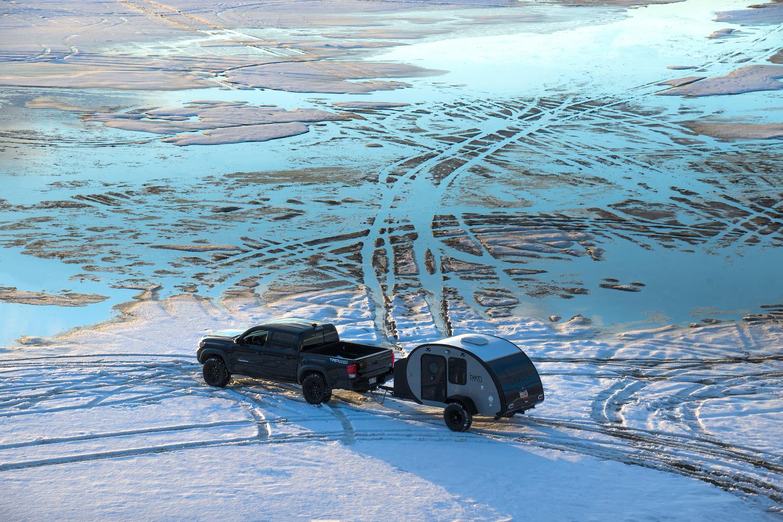 THE GREAT SALT LAKE, UTAH / UNITED STATES - January 23, 2019: Toyota Tacoma Pulls Teardrop Trailer onto Frozen Lake