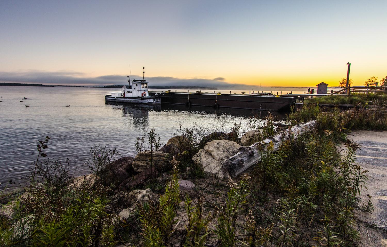Lake Superior Sunrise. Small tugboat moored on a Lake Superior dock with a coastal sunrise in the background. Grand Island National Recreation Area. Munising, Michigan.