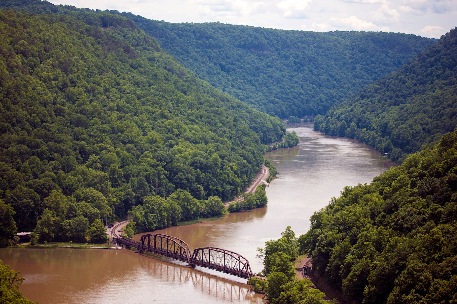 The graceful curves of the Gauley River in West Virginia with lush summer forest rising sharply from its' banks, a train tressel crossing near the bottom of the image.
